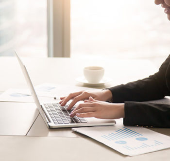 Close-up side view of serious businesswoman working at office desk on laptop, typing and looking at screen, surrounded by diagrams and calculating charts. Business, finances, economics and technology