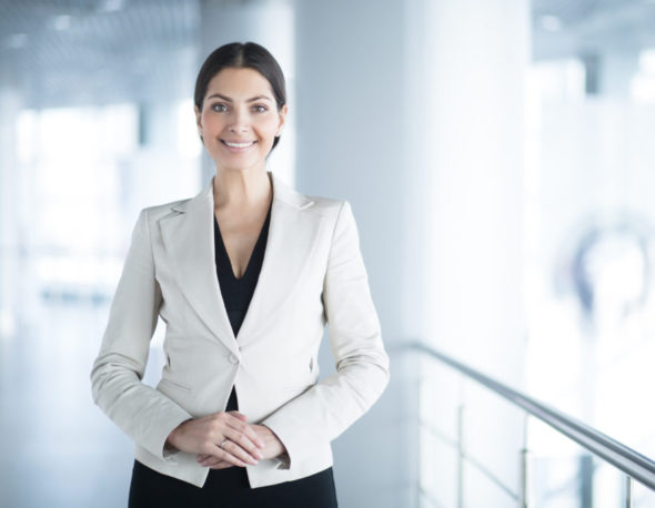 Closeup portrait of smiling beautiful middle-aged business woman wearing jacket, looking at camera and standing in light office hall